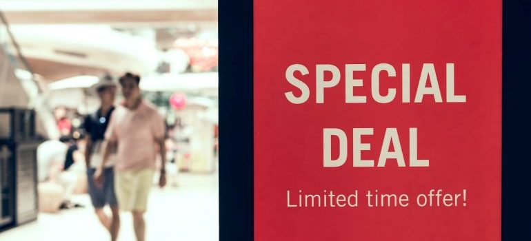 A poster showing special deal discounts, and two people walking in the background.