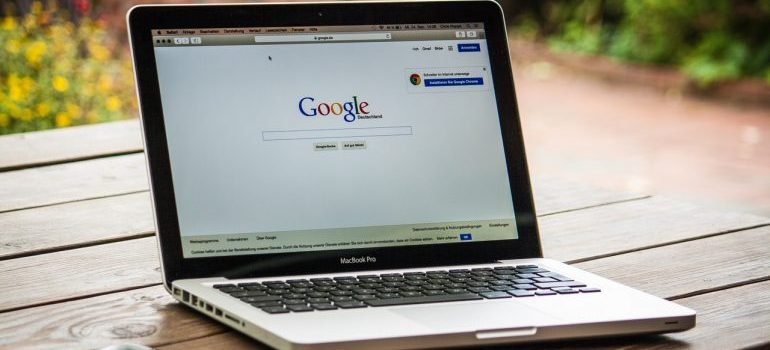 A laptop on a table with a Google tab opened in a browser.