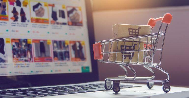 Shopping cart next to laptop screen.