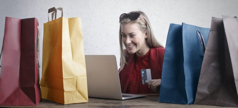 Woman holding a credit card while looking at laptop, surrounded by shopping bags.