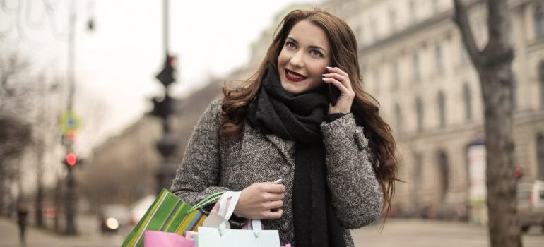 Woman with shopping bags, talking on her phone.