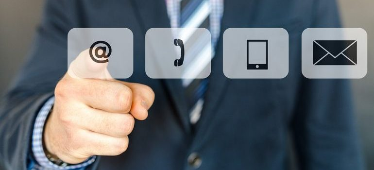 A man in a suit pointing to contact icons.