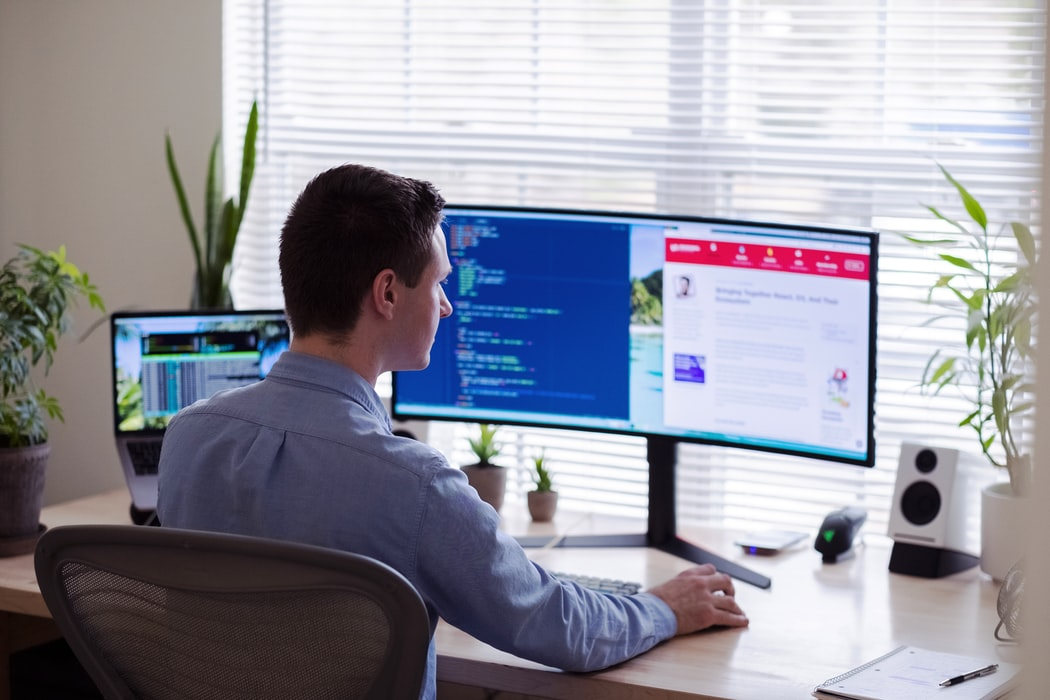 Person working at a two-monitor computer.