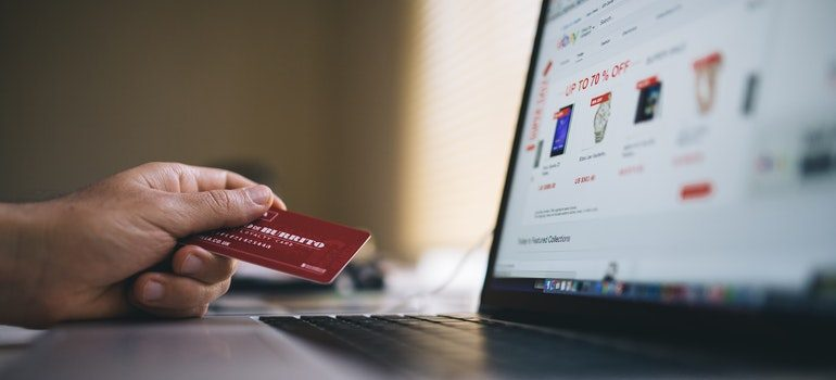 Person holding a credit card in front of a laptop.