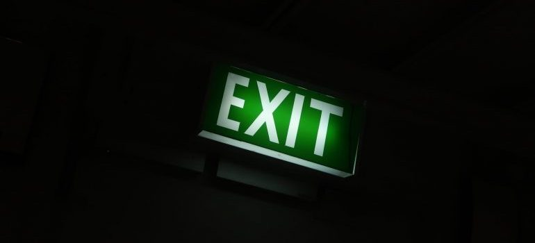 A green exit sign over a black background.