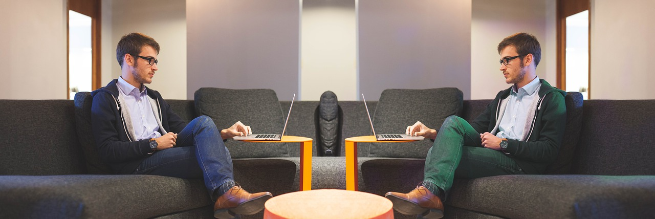 A man in a blue outfit sitting across its double in a green outfit, representing the differences of inbound vs outbound sales tactics.
