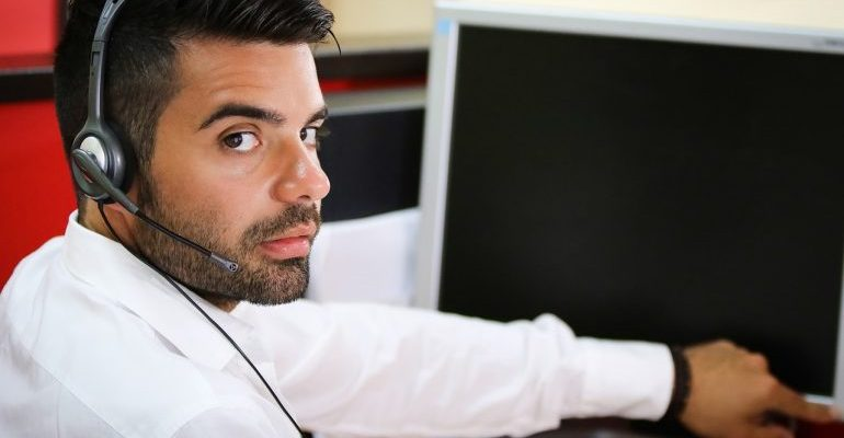 A call center representative in a white shirt with a brand new headset.