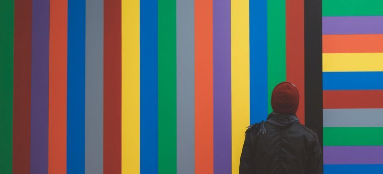 A man looking at a colorful wall.